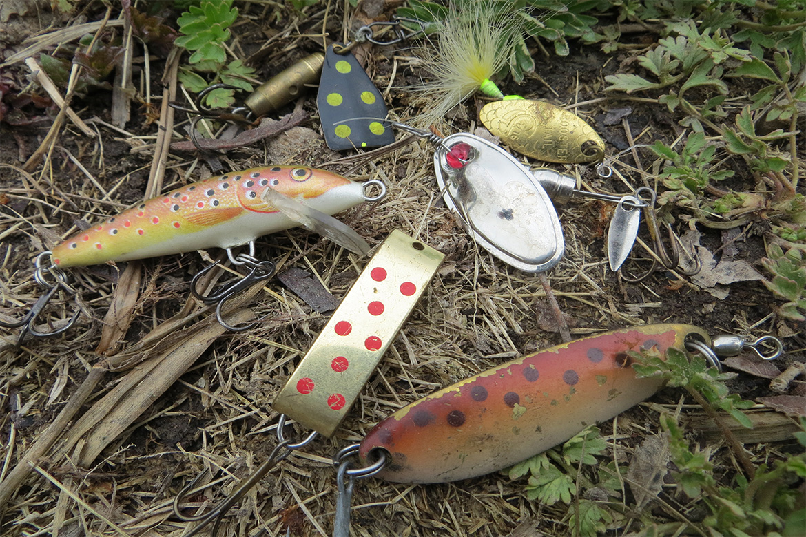 trout lures sitting on the bank by a river