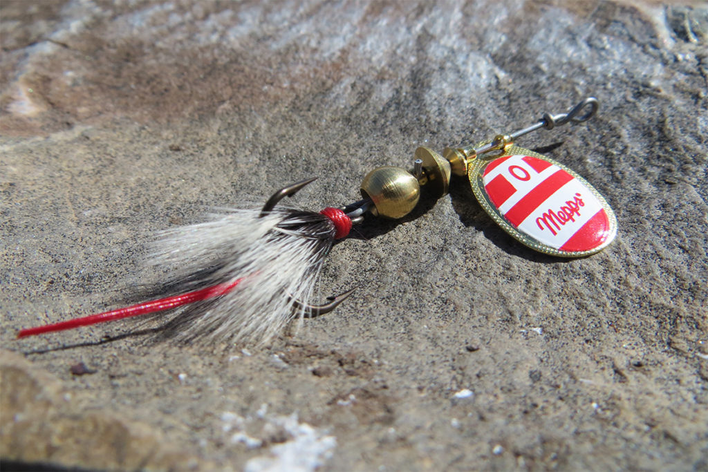 meps red and gold spinner sitting on a rock by a steam